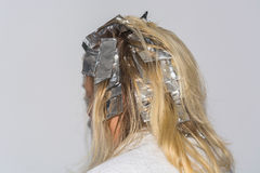 Hair highlights wrapped in aluminum foil. Woman with blond hair in preparation for hair dyeing. Hair highlights wrapped in aluminum foil stock photography