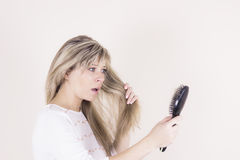 Hair loss. Depressed young woman looking at her hairbrush and expressing negativity.  Stock Photo
