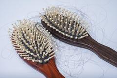 Hair loss problem on brush, on white background. Women postpartum defluvium Stock Photography