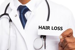 Hair loss text on card presented by doctor. Hair loss black text on white card presented by indian male doctor wearing lab coat close-up stock photos
