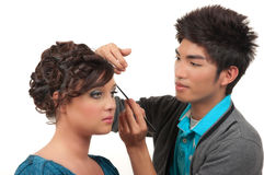 Hair And Make Up. Cosmetics artist doing finishing touches of her customer's hair and make up before her prom, wedding royalty free stock photo