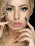 Hair and make-up theme: beautiful girl with beautiful golden nail in the studio Royalty Free Stock Photos