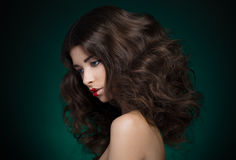 Hair and make-up topic: a very beautiful girl model with lush hair and creative make-up on blue-green background Stock Photography