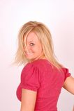 Hair Model. Pretty young blonde woman turns with back to camera and smiles while wearing a red shirt Royalty Free Stock Image