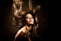Hair in motion. Beautiful woman with long golden hair in motion, studio shot Stock Image