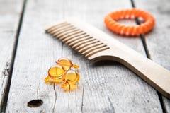 Hair nurishment. vitamin serum capsule on wooden background Stock Photography