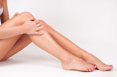 Hair removal and epilation. Woman legs with smooth skin after depilation. Long woman legs with smooth skin after depilation. Female hand touching perfect Stock Photography