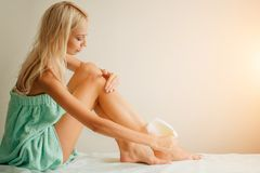 Beautiful woman doing depilation for her legs with waxing strip Stock Photography