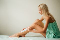 Beautiful woman doing depilation for her legs with waxing strip Royalty Free Stock Images