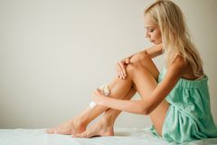 Beautiful woman doing depilation for her legs with waxing strip Stock Image