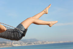 Hair removed woman legs swinging on the beach Stock Photos