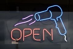 Hair Salon Center Sign with Blow dryer. A hair salon center sign with a blow dryer reads open, outside of a hair salon shop Royalty Free Stock Image