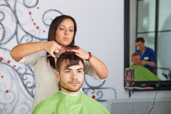 Hair salon. Hairdresser does haircut for man. Royalty Free Stock Images