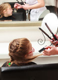 In hair salon. Little girl child sitting by hairdresser combing hair Royalty Free Stock Images