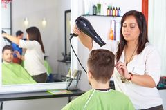 Hair salon. Men`s haircut. Use of hair dryer. Royalty Free Stock Photo