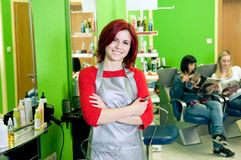 Hair salon owner or employee. Happy hair salon owner or employee with customers in the background Stock Photos