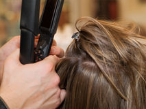 At The Hair Salon. Using hair straightener shot from above Stock Image
