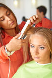 Hair salon. Woman haircut. Use of straightener. stock photo
