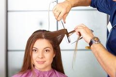 Hair salon. Woman haircut. Use of straightener. Stock Photo