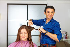 Hair salon. Woman haircut. Use of straightener. Royalty Free Stock Images