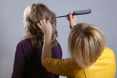 Hair salon. Woman hairstyle. Hairdresser combing hair of client. Rear view. Royalty Free Stock Photography