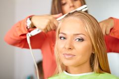 Hair salon. Women`s haircut. Use of straightener. Stock Photo