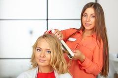 Hair salon. Womens haircut. Use of straightener. Stock Photos