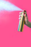 Hair spray. Photo of hair lacquer in female�s hand spraying it over red background Royalty Free Stock Images