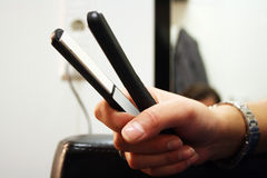 Hair Straightener. Master hairdresser cuts a customer's hair Royalty Free Stock Photo
