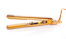 Hair straightener. A golden hair straightener isolated on white background Royalty Free Stock Photos