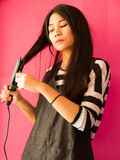 Hair straighteners. Asian girl dressing her hair with hair straighteners Royalty Free Stock Photos