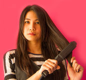 Hair straighteners. Asian girl dressing her hair with hair straighteners Royalty Free Stock Photography