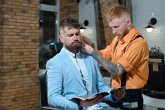 Hair style and hair stylist. Beard man visiting hairstylist in barber shop. Client getting haircut by hairdresser. Hair style and hair stylist. Beard men royalty free stock images