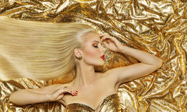 Hair Style Model, Fashion Long Straight Hairstyle, Gold Woman. Hair Style Model, Fashion Long Straight Hairstyle, Woman Lying on Gold Color Cloth Royalty Free Stock Images