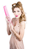 Hair style model. Pinup girl with large pink comb Royalty Free Stock Photography
