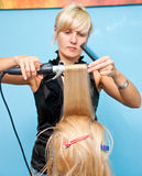 Hair styling in a beauty salon. A hairdresser is styling blond women's hair Stock Photos