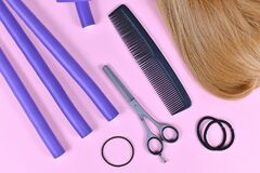 Hair styling concept with dark blond hair, elastic hair ties, comb, thinning shears, and papillote curlers