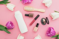 Hair styling concept with shampoo, combs, cosmetics and flowers on pink background. Flat lay, top view. Hair styling concept with shampoo, combs, cosmetics and Royalty Free Stock Images