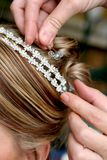 Hair Stylist. Putting beads in brides hair for decoration Stock Images