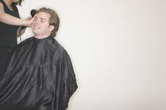 Hair stylist. Young man sitting in a chair getting his hair worked on by a hair stylist Royalty Free Stock Image