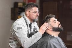 Hair stylist applying after shaving lotion at barber shop. royalty free stock photos