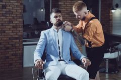 Hair Stylist and Barber. Hair salon and barber vintage. Brutal guy in modern Barber Shop. Trims. Great time at. Barbershop. Barber making haircut of attractive royalty free stock photos