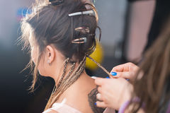 A hair stylist braids a young and beautiful girl. Zizi cornrows Stock Images