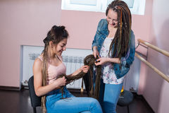 A hair stylist braids Zizi cornrows to a young and beautiful girl Royalty Free Stock Photos