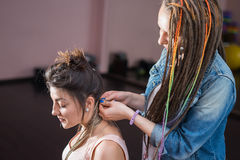 A hair stylist braids Zizi cornrows to a young and beautiful girl Stock Photos
