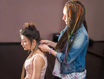 A hair stylist braids Zizi cornrows to a young and beautiful girl Royalty Free Stock Images