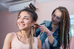 A hair stylist braids Zizi cornrows to a young and beautiful girl Stock Photography