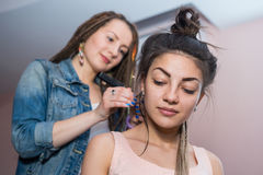 A hair stylist combs hair to make Zizi cornrows Stock Photos