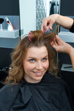 Hair stylist curling woman hair in salon Stock Photos