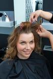 Hair stylist curling woman hair in salon Stock Photos